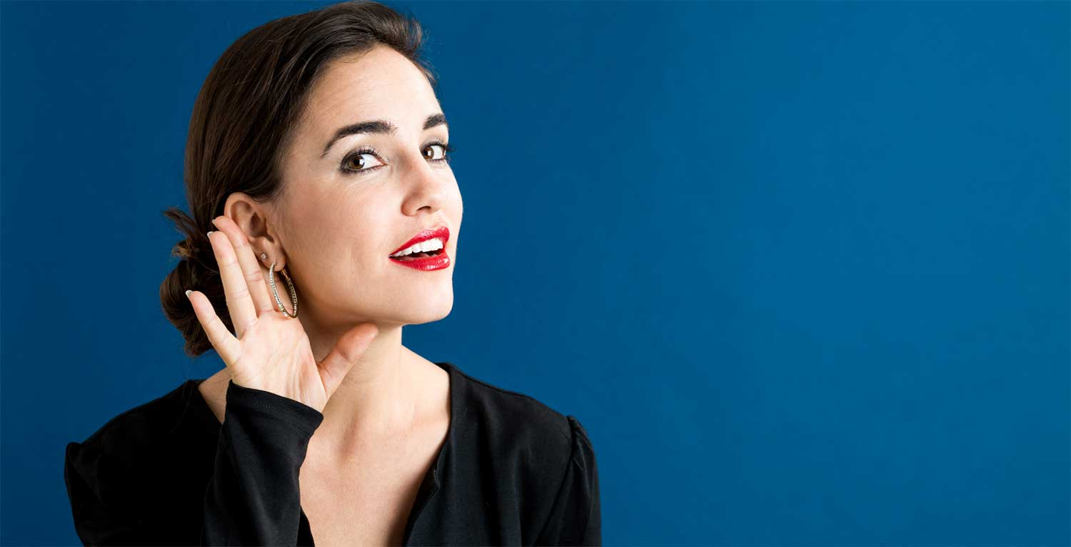 Woman holding up a  hand against ear signifying professional skill of active listening
