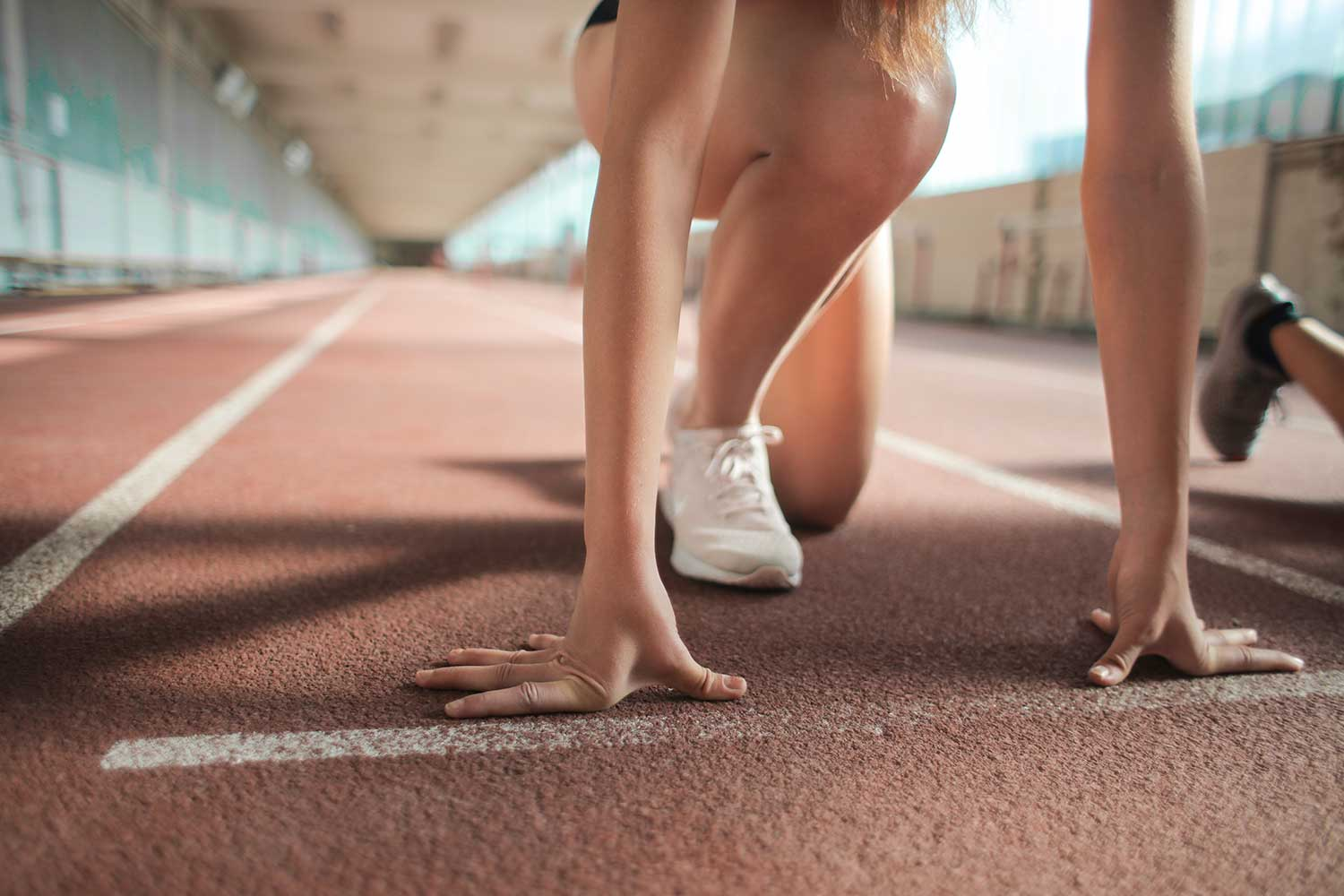 Closeup of woman kneeling down by starting line