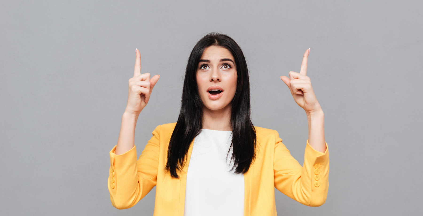 Woman in yellow blazer pointing upward with both hands symbolising professional growth