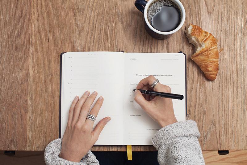 Woman writing in black diary