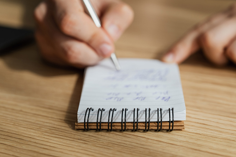 Man writing in notebook with pen after giving constructive feedback