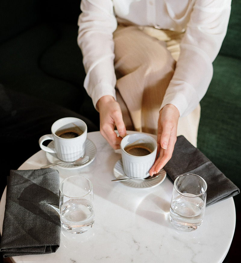 Woman holding white ceramic cup sitting at a table